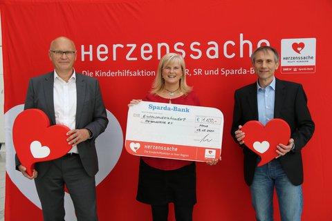 Jürgen Springer und Frank Heuser (v.l.n.r.) vom BARMER Beitragszentrum Frankfurt übergeben den Spendenscheck an Sandra Filtzinger von Herzenssache