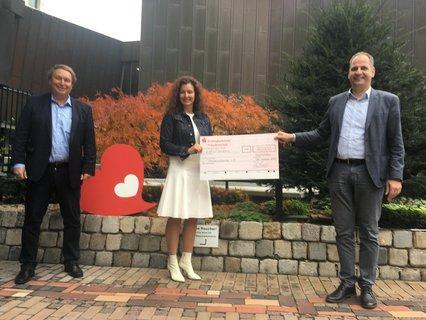 Herr Haas und Herr Schabel (Geschäftsführer der farbtex GmbH) übergeben den Spendenscheck in Höhe von 10.000 Euro an Herzenssache-Botschafterin Christian Benz